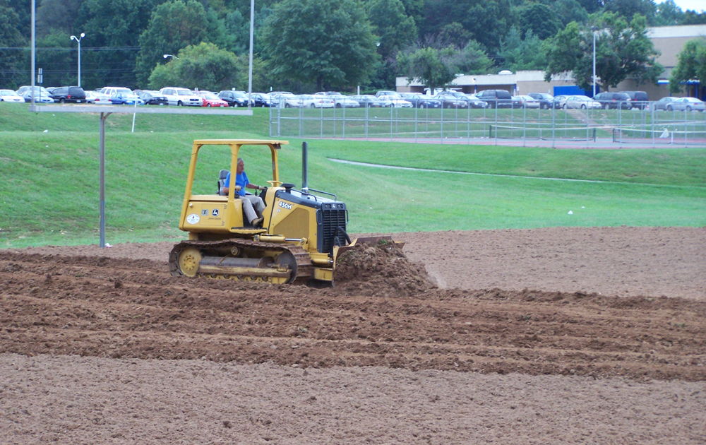 Tractor pushing dirt on an athletic field.